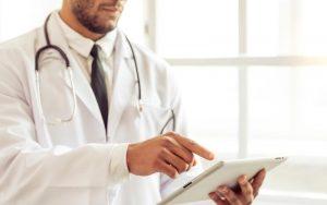 A imagem mostra um médico, de pele branca, utilizando um tablet. Ele usa um jaleco branco e um estetoscópio preto com prata sobreposto em seus ombros. Por baixo do jaleco, é possível visualizar uma camisa clara e uma gravata preta. Ele está voltado para o lado direito da imagem, em pé, segurando um tablet branco com sua mão esquerda, enquanto seu dedo indicador direto toca a tela.