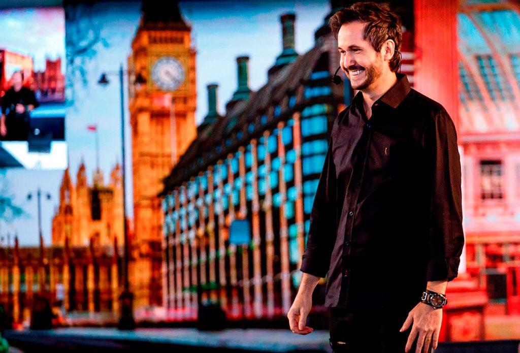 Foto do Mario Lago no palco em um evento da London cosméticos. Ele está olhando para a esquerda, sorrindo. Mario usa uma roupa toda preta.